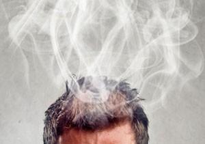 Hombre-pensando-con-los-ojos-cerrados-poniendo-sus-dedos-sobre-sus-sienes-mientras-le-sale-humo-de-su-cabeza